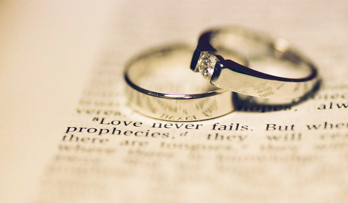 wedding rings on top of paper that says love never fails