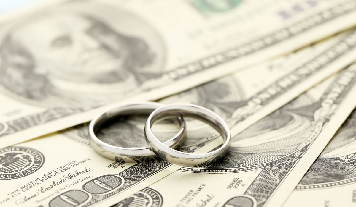 wedding rings sitting on top of money