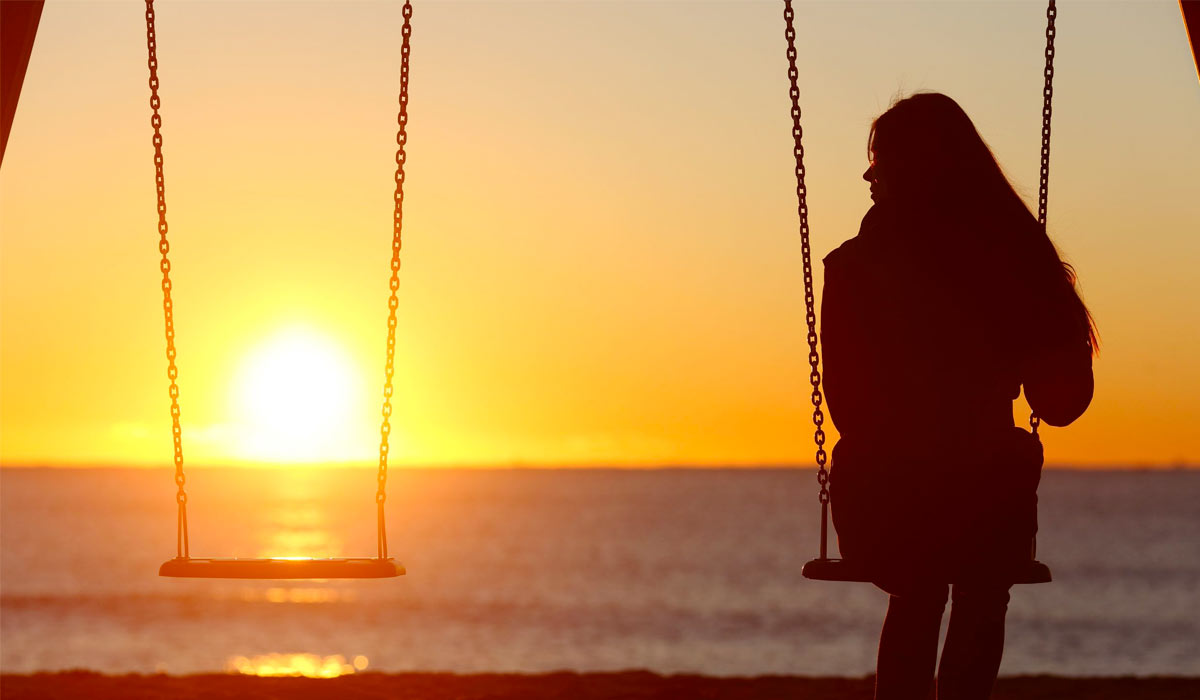 woman alone on swing set looking at sunset