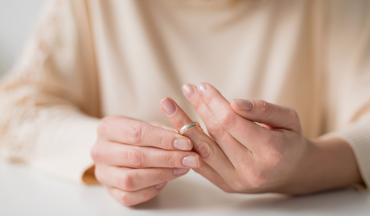 woman contemplating divorce taking off wedding ring