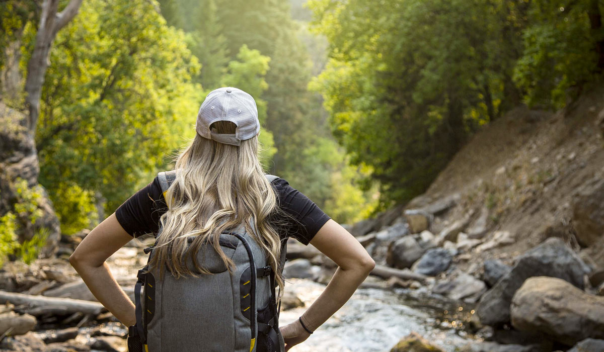 woman hiking near a river stream