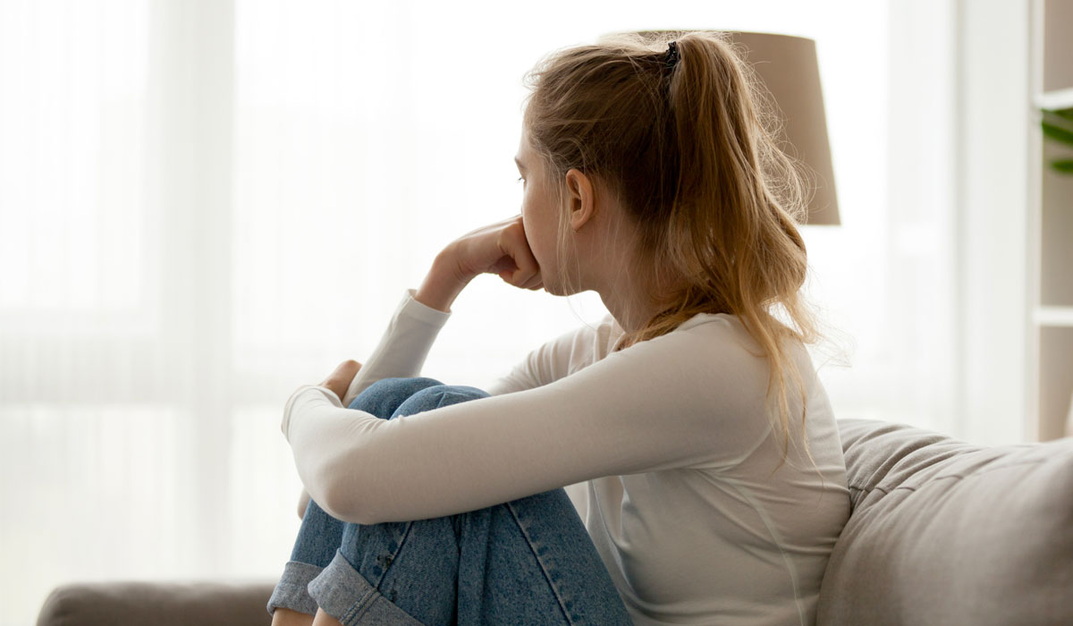 woman looking distraught on couch staring out the window