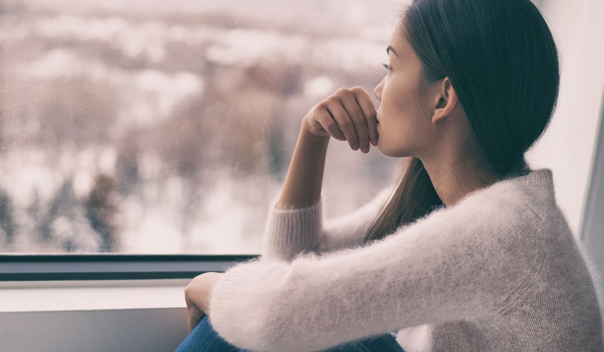 woman looking out window feeling sad