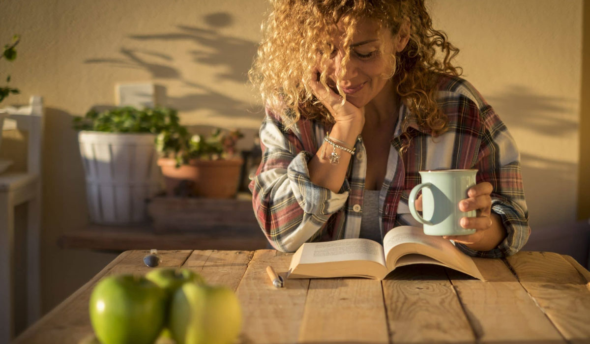 woman reading book alone with coffee in hand