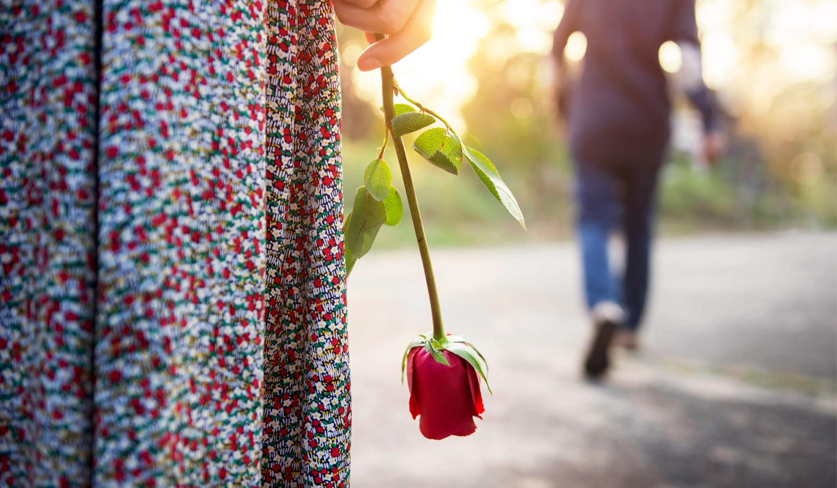 woman standing with rose left alone with man walking away