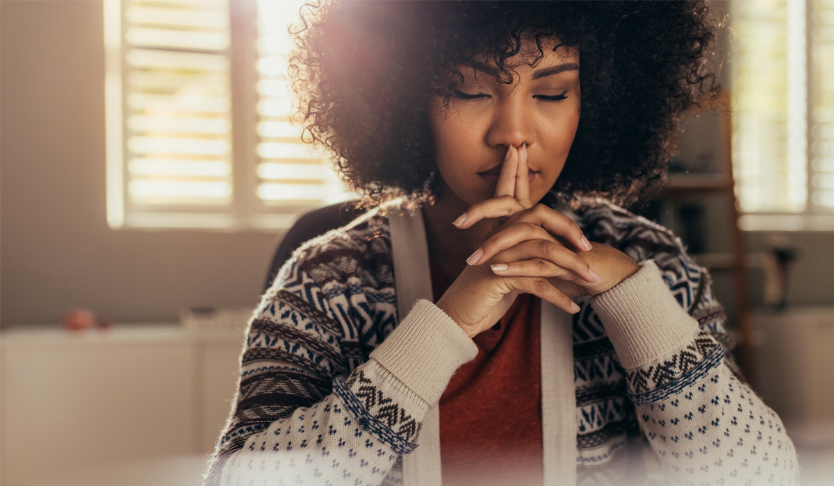 woman with interlocked hands deep in thought