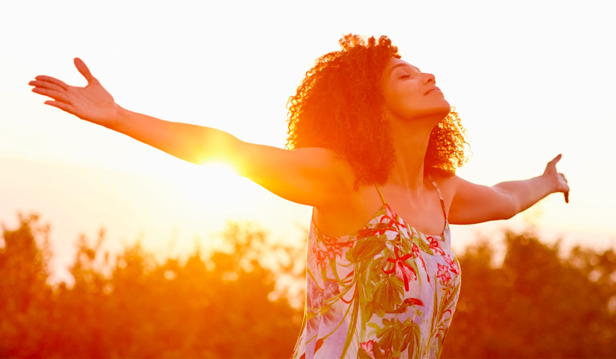 woman with outstretched arms with sunset in background