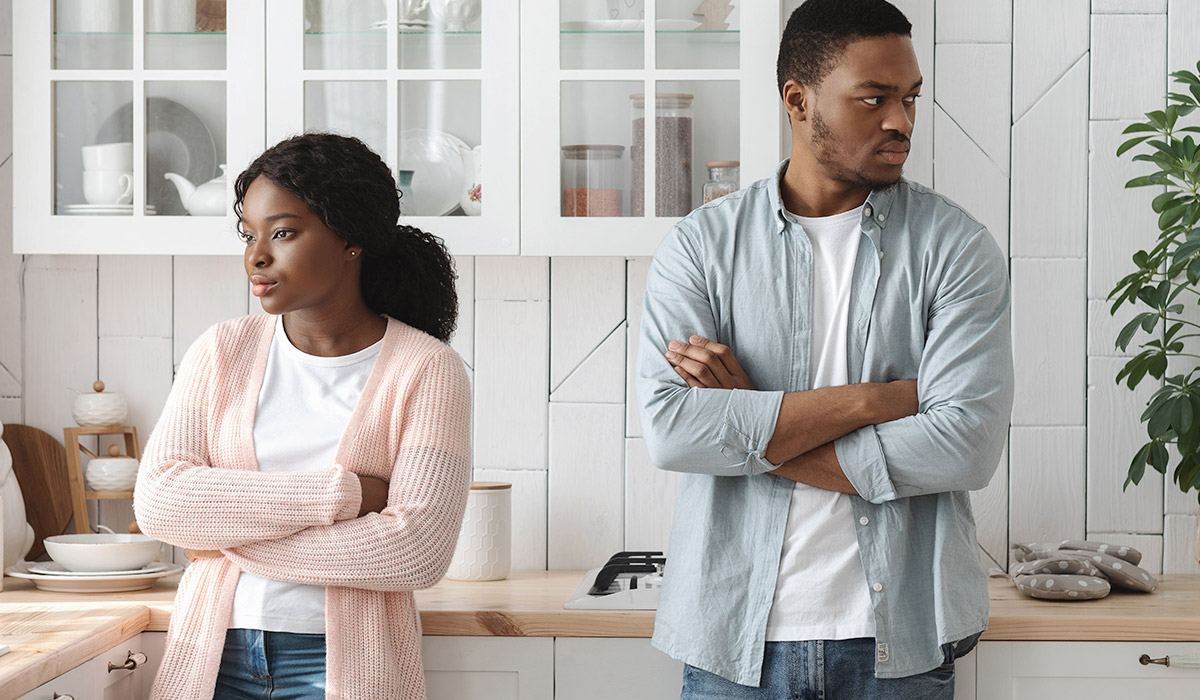 young couple looking angry at each other standing with crossed arms