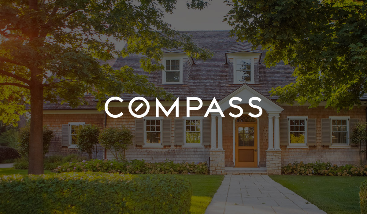 compass real estate logo on house background
