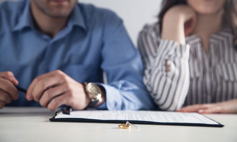 couple sitting in front of divorce papers