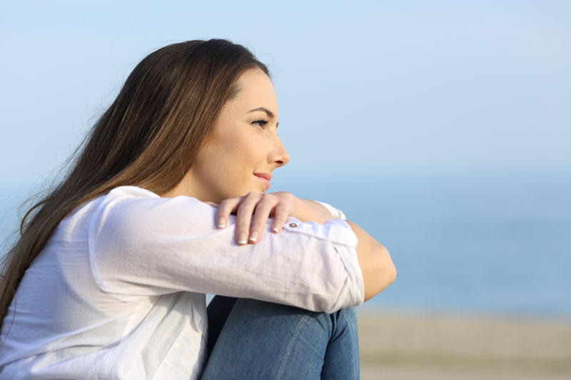 woman sitting with crossed arms looking into the distance