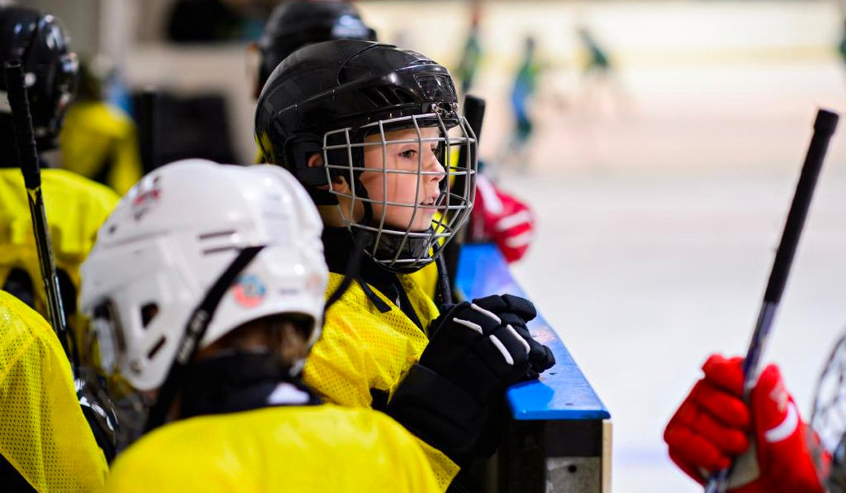 child in hockey gear on the sidelines looking out into the ice