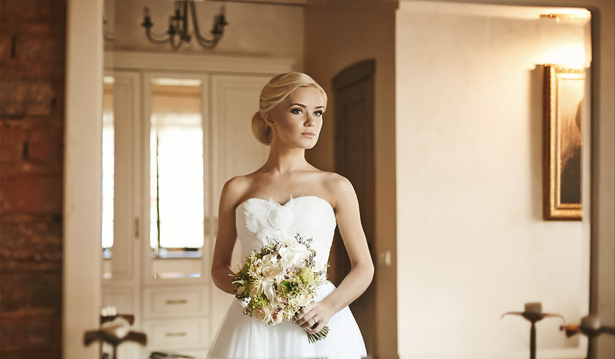 Beautiful bride holding a bouquet with a serious expression on her face looking at herself in the mirror