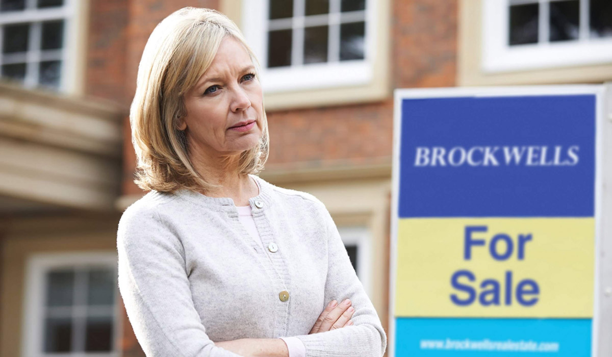 upset woman looks into the distance next to a for sale sign outside of her home