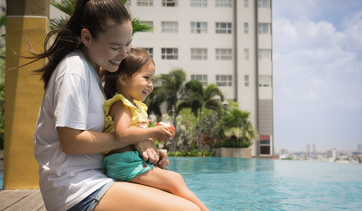 mother and daughter smiling and sitting at the edge of a pool outside a hotel