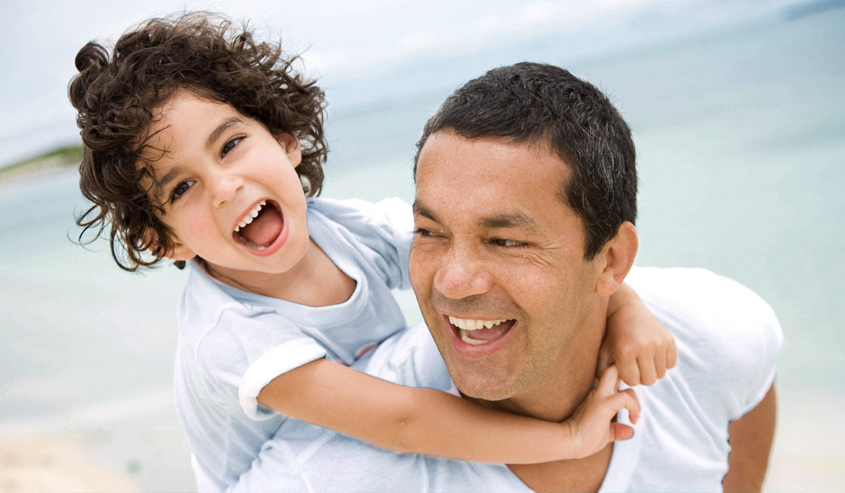 father and son smiling and laughing at the beach